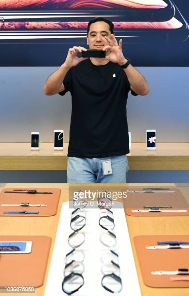 An Apple staff member photographs the new Apple watch models at the Australian release of the latest iPhone and watch models at the Apple Store on...