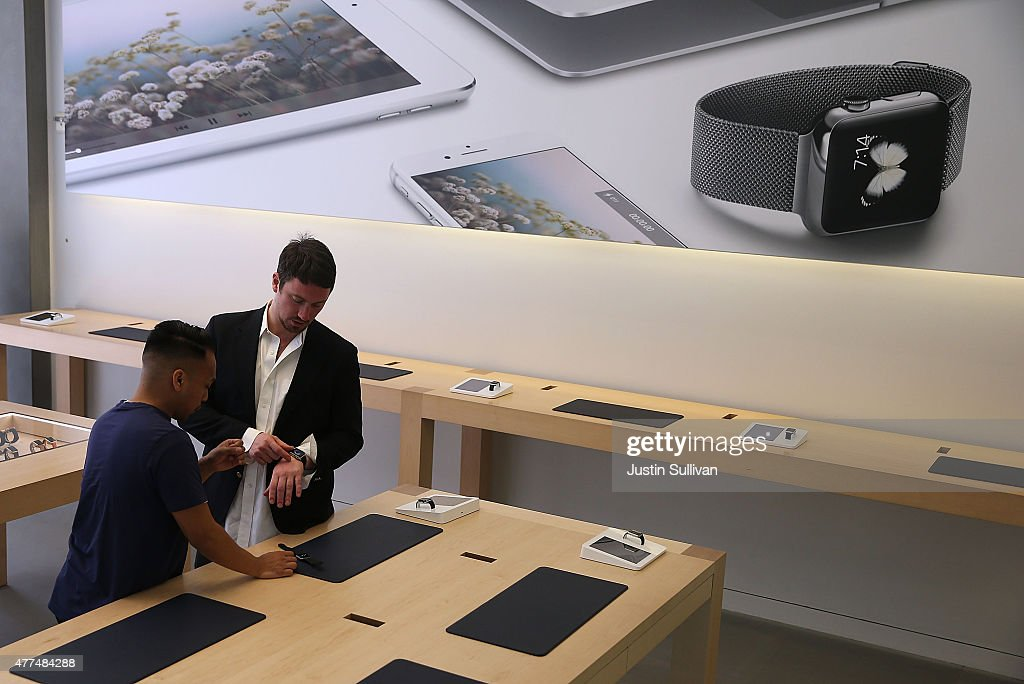 An Apple Store employee helps a customer with the new Apple Watch at the Apple Store on June 17, 2015 in San Francisco, California. Apple began selling the Apple Watch in its stores Wednesday with their reserve and pick up service. Previously the product could only be ordered online.