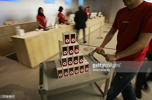 An Apple store employee pushes a cart of RED iPod nanos sit in the Apple store in midtown Manhattan October 13 2006 in New York Apple computer is...