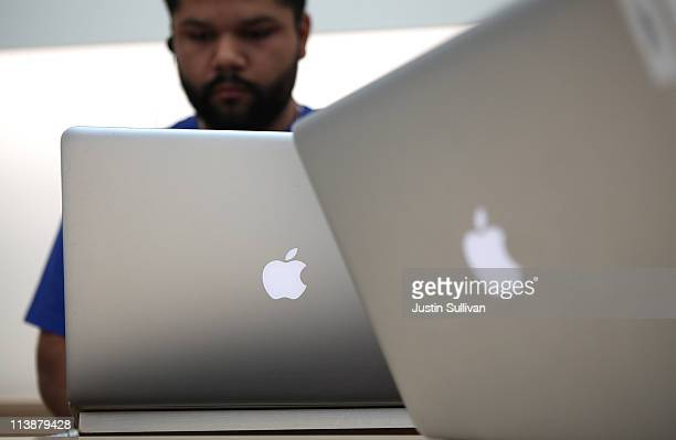An Apple Store genius bar employee works on a laptop at an Apple Store following an announcement that Apple has become the world's most valuable...