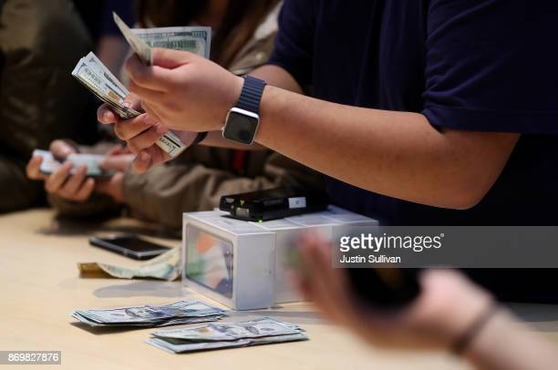 An Apple Store worker counts money as they sell the new iPhone X on November 3 2017 in Palo Alto California The highly anticipated iPhone X went on...
