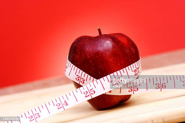 An apple with a measuring tape