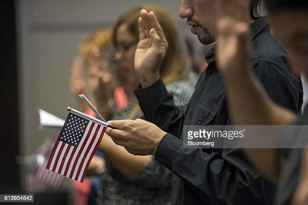 An applicant for US citizenship holds an American flag while taking the Oath of Allegiance during a naturalization ceremony at the Evo A DeConcini US...
