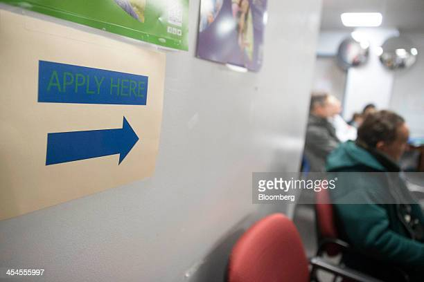 """An """"Apply Here"""" sign hangs at a health insurance education and enrollment event in Silver Spring, Maryland, U.S., on Saturday, Dec. 7, 2013...."""