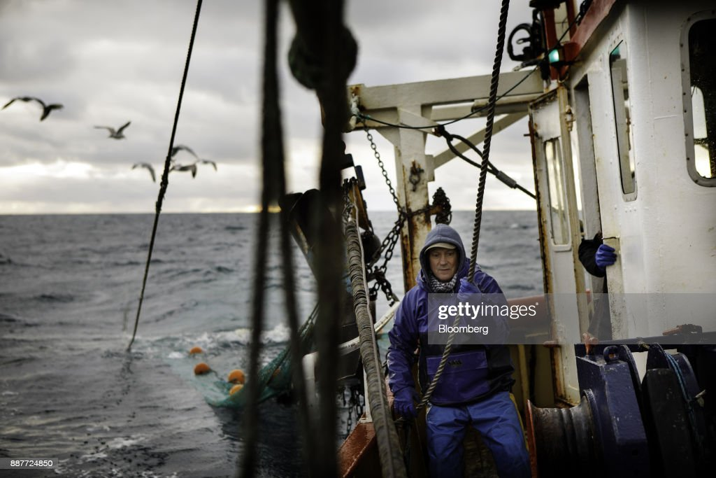 An apprentice fisherman hauls in a fishing net aboard the Harvest Reaper fishing trawler while sailing approximately 18 nautical miles offshore from Newlyn, U.K., on Sunday, Nov. 26, 2017. Prime Minister Theresa May will pull Britain out of the 1964 London convention that allows European fishing vessels to access waters as close as six to twelve nautical miles from the U.K. coastline. Photographer: Annie Sakkab/Bloomberg via Getty Images
