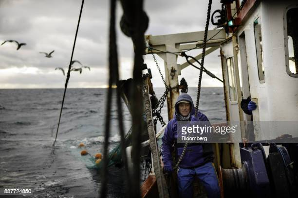 An apprentice fisherman hauls in a fishing net aboard the Harvest Reaper fishing trawler while sailing approximately 18 nautical miles offshore from...