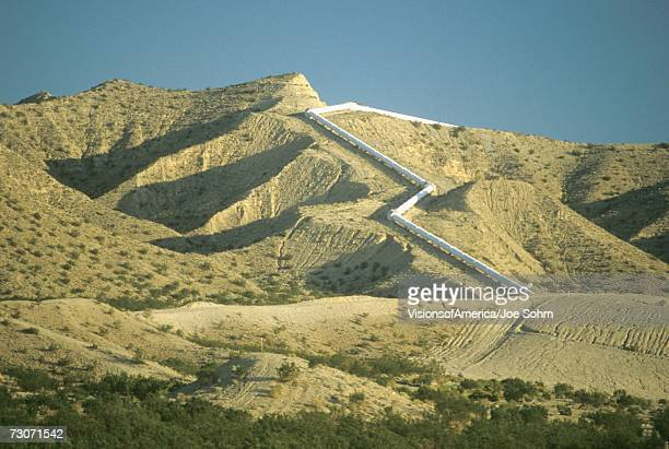 An aqueduct which supplies water to Los Angeles winding down a hill in the California desert