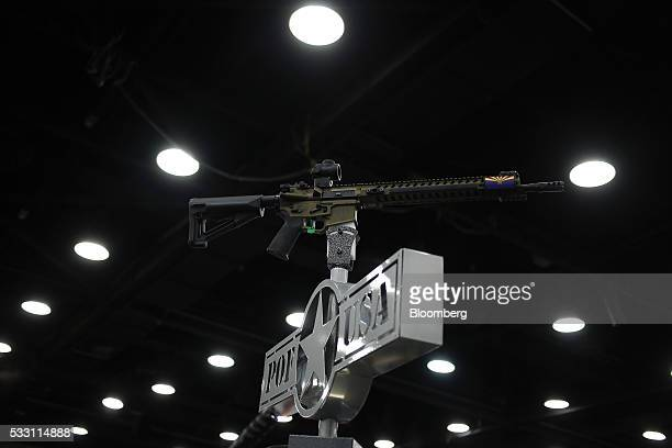 An AR15 rifle is displayed on top of a booth on the exhibit floor during the National Rifle Association annual meeting in Louisville Kentucky US on...