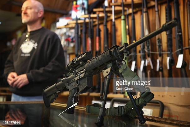 An AR15 style rifle sits on the counter by Craig Marshall as he assists a customer at Freddie Bear Sports sporting goods store on December 17 2012 in...