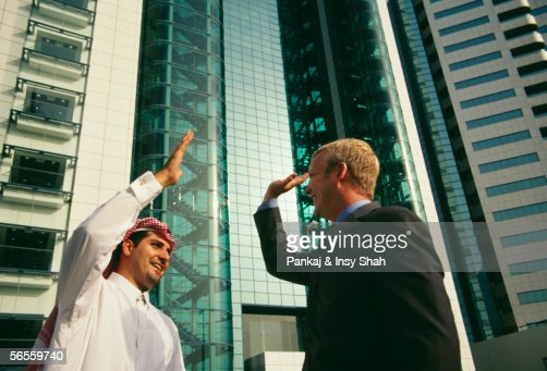 An arab and a businessman greeting each other happily near a an arab and a businessman greeting each other happily near a commercial complex stock photo getty images m4hsunfo