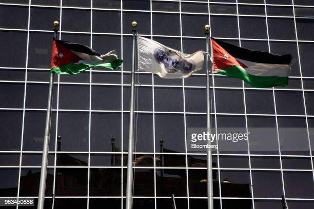 An Arab Bank flag flies between two Jordanian national flags at the Arab Bank Plc headquarters in Amman Jordan on Thursday June 21 2018 President...