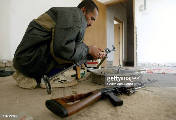 An Arab fighter cleans his weapons on November 7 2004 in the city of Fallujah Iraq The Mujahadeen are preparing for a major US offensive against...