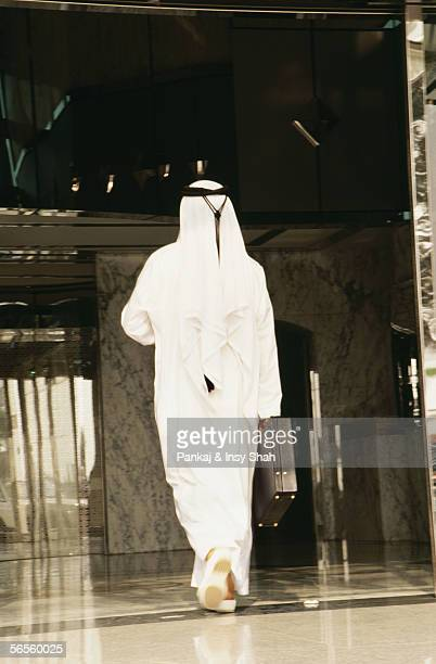 An Arab in traditional dress enters a commercial building.