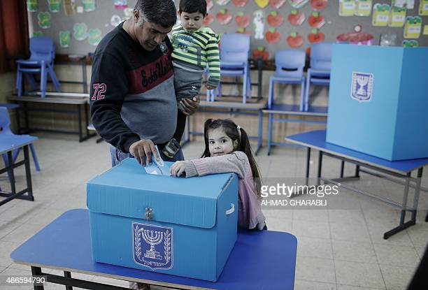 An Arab Israeli man casts his ballot at a polling station in the northern Israeli town of Umm alFahm on March 17 2015 Voting polls opened for...