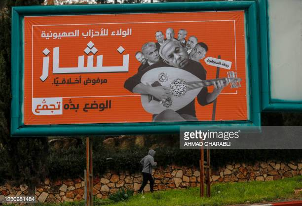 """An Arab Israeli man jogs past a campaign billboard for the Balad Party, part of the joint Arab list, which reads in Arabic """"Loyalty to zionist..."""