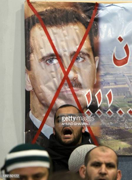 An Arab Israeli man shouts slogans as he stands in front of a crossedout picture of Syrian President Bashar alAssad during a rally against the Syrian...