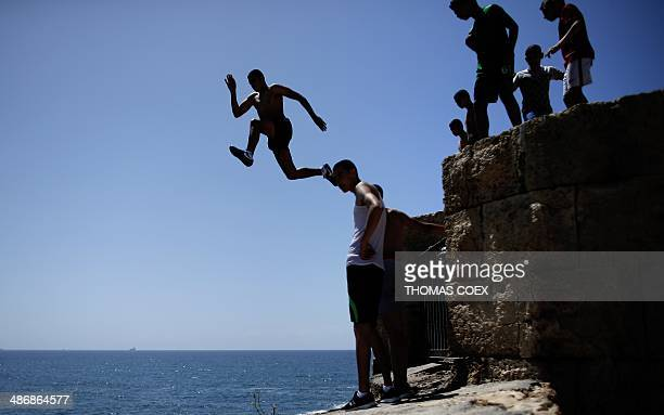 An Arab Israeli teenager jumps from the ramparts into to the Mediterranean sea as his comrades look on on April 26 2014 in the ancient Mediterranean...
