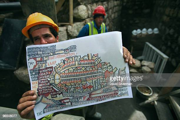 An Arab labourer holds a copy of the famous Madaba map an ancient mosaic map to be found in a church in Jordan dated to the sixthseventh century AD...