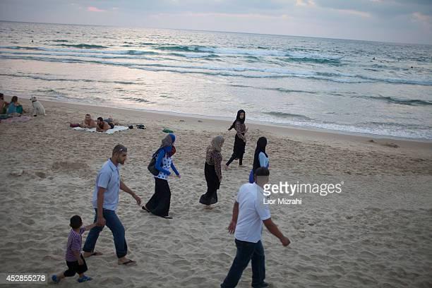 An Arab Muslim Israeli family walks on the beach on the first day of Eid alFitr on July 28 2014 in Tel Aviv Israel As Israel's operation 'Protective...
