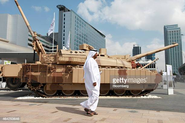 An Arab visitor walks past a battle tank displayed outside the International Defence Exhibition in Abu Dhabi United Arab Emirates on Monday Feb 23...