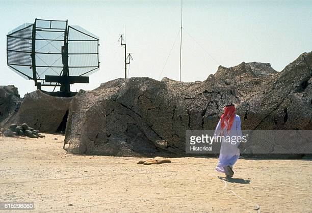 An Arab walks toward camouflaged equipment and ANTPS43 search radar in a US military base camp during Operation Desert Shield