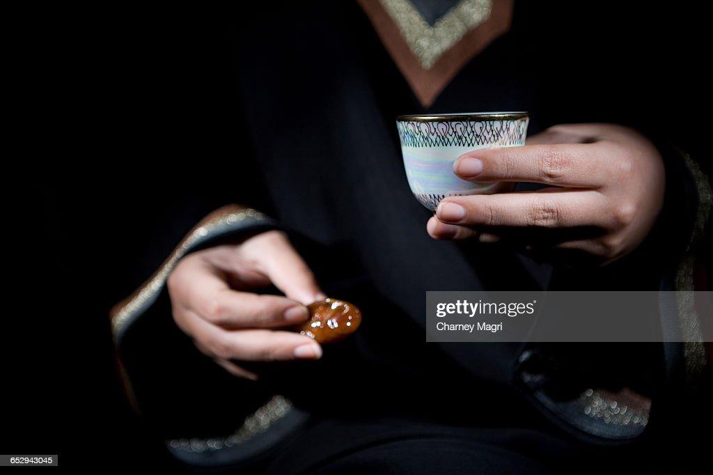 An arab woman holding a bowl of dates and gawa (Arabian Coffee). : Stock Photo