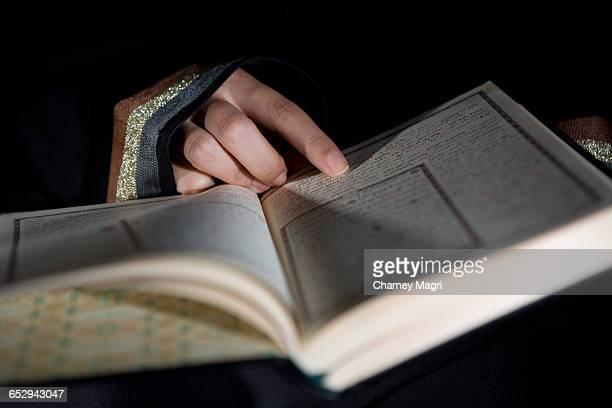 An arab woman reading the Holy Quran.