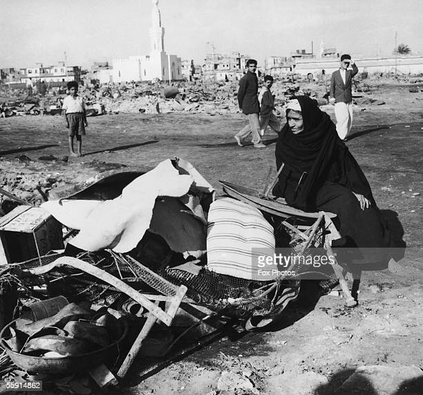 An Arab woman sits amidst her salvaged belongings in a ruined area of Port Said during the Suez Crisis, 12th November 1956.