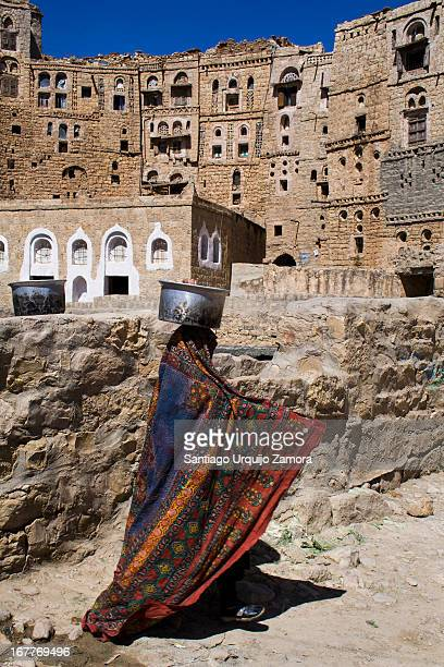 CONTENT] An Arab woman wrapped with colored embroidery abaya or cloak carrying water on her head The water was taken from a water cistern at Hababah...