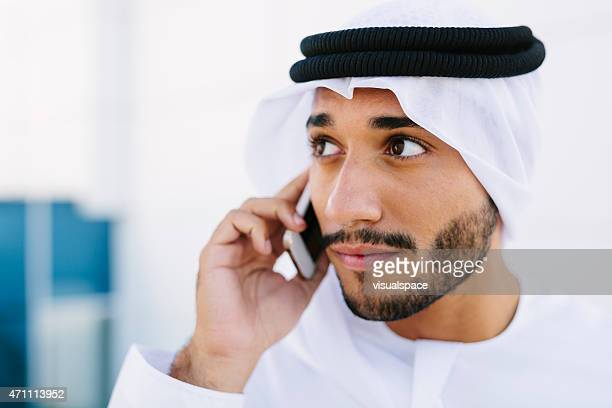 An Arabian man with brown eyes on the phone