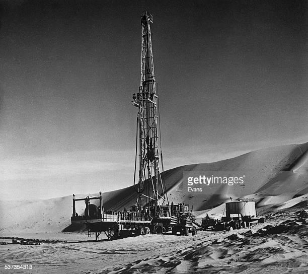 An ArabianAmerican Oil Company drilling rig at Rub' al Khali in the Arabian Peninsula Saudi Arabia circa 1955 The ArabianAmerican Oil Company was...