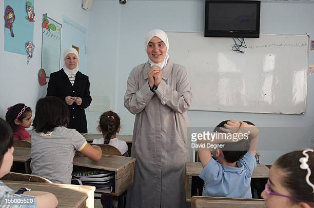 An Arabic language teacher at Bumat Alajial school introduces one of the new students to the class after she arrived late September 18 2012 Tuesday...