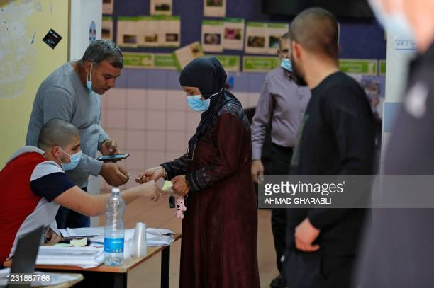 An Arab-Israeli voter, wearing a protective mask against the COVID-19 pandemic, registers before casting her vote on March 23, 2021 in the fourth...