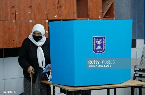 An Arab-Israeli voter, wearing a protective mask against the COVID-19 pandemic, votes on March 23, 2021 in the fourth national election in two years...