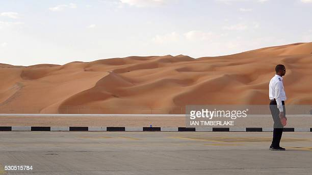 An Aramco staff member stands on a road at the Saudi Aramco airport surrounded by sand dunes at the Shaybah oilfield some 800 kilometers southeast of...
