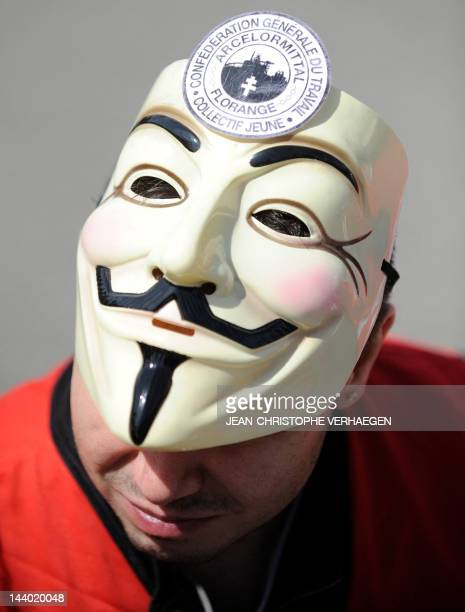An ArcelorMittal steel worker from the plant in the French city of Florange wears a Guy Fawkes mask while demonstrating in front of ArcelorMittal...