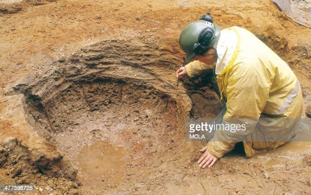 An archaeologist carefully excavating a construction pit lined with wattle which would have later been filled with a wooden barrel acting as a shaft...