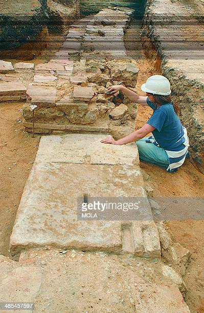 An archaeologist cleaning the masonry doorway leading into a side chamber for wild animals to the left with London's Roman amphitheatre arena to the...