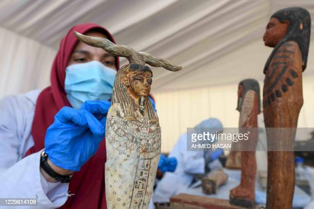 An archaeologist cleans a statue during the unveiling of an ancient treasure trove of more than a 100 intact sarcophagi at the Saqqara necropolis 30...