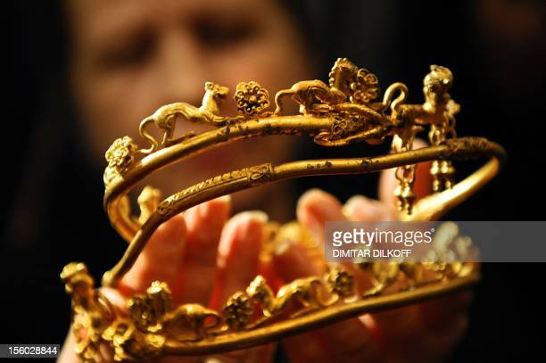 An archaeologist displays a gold tiara engraved with a lion's head and other animals part of a Thracian treasure at the Archaeology Museum in Sofia...