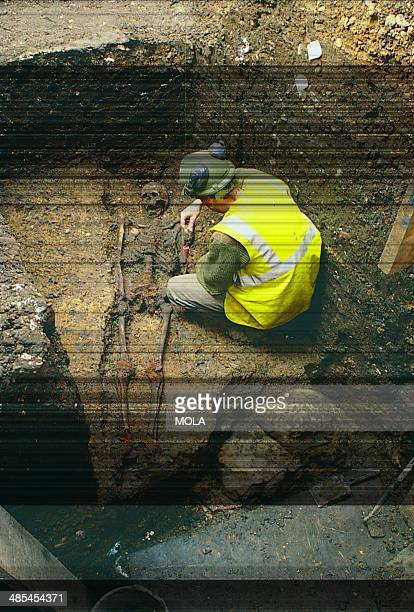 An archaeologist examining a human skeleton found just behind the small fragment of wall in the southern entranceway to London's Roman amphitheatre's...