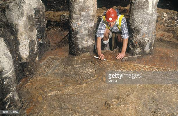 An archaeologist excavating a complex geometric patterned mosaic floor within a late Roman addition to one of the properties possibly a wealthy...