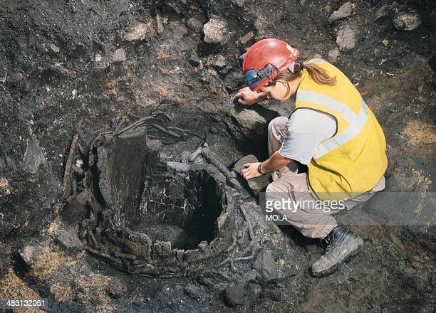 An archaeologist excavating a Late Saxon well located in an external area between Bucklersbury and Poultry it was constructed from part of a single...