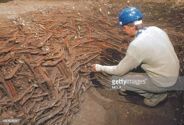 An archaeologist excavating a wattlelined square pit which would have served as a well 12th to 13th century from the 19928 excavations at Guildhall...