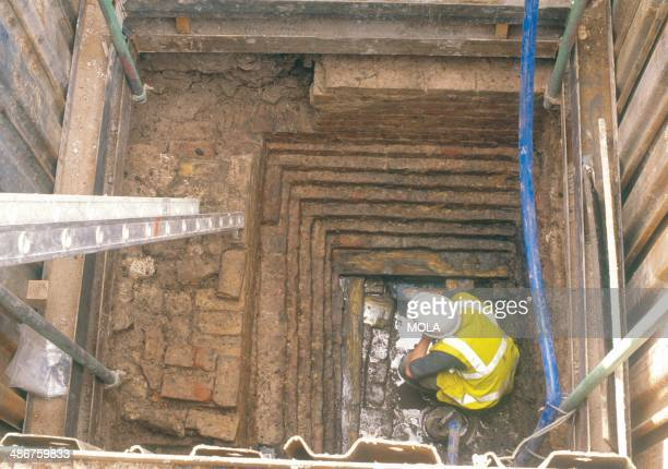 An archaeologist excavating the deep stepped brickwork founded on a series of tangentially faced pine beams and planks as shown on George Dance's...