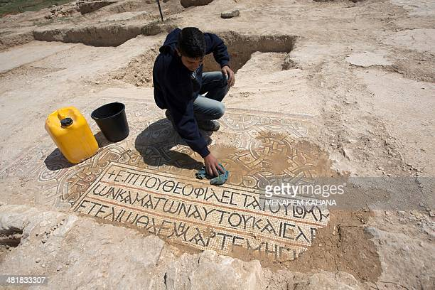 An archaeologist unveils Greek inscriptions as he cleans a Byzantine mosaic floor that decorated a monastery and that was discovered during...