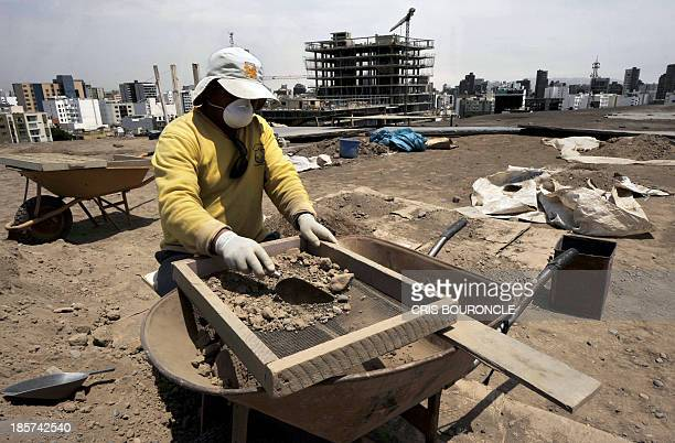 An archaeologist works at the preInca religious complex 'Huaca Pucllana' in the residential district of Miraflores in Lima on October 24 2013 day in...