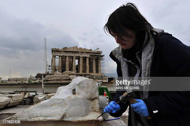 An archaeologist works on marble at the top of the Acropolis hill in Athens on January 2011 Like the victory goddess it honours Athens' ancient...