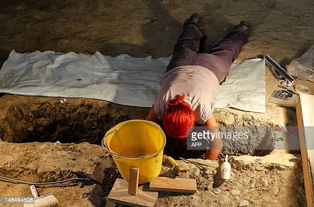 An archaeologist works on the excavation of a grave inside the medieval Convent of Saint Ursula in Florence on July 17 during research for the burial...