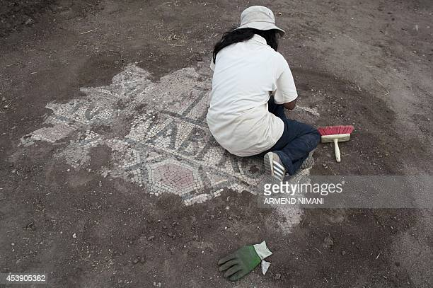 An archaeology student unearths a mosaic in an excavation at the archeological site of the ancient city of Ulpiana near the town of Gracanica south...
